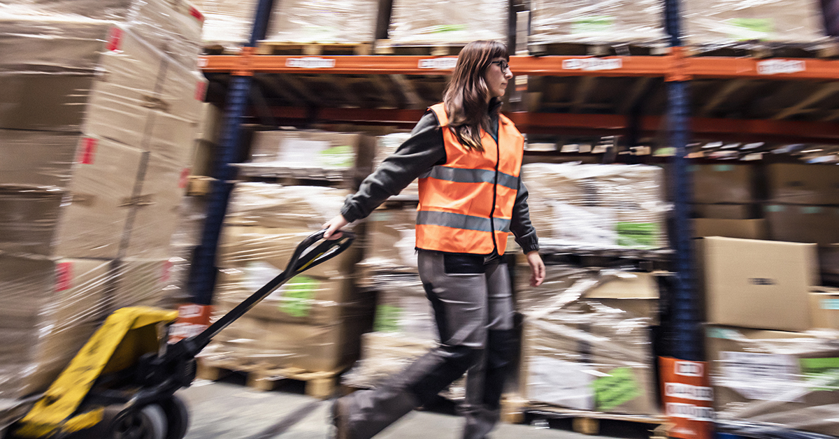 Young woman moving boxes in a warehouse.